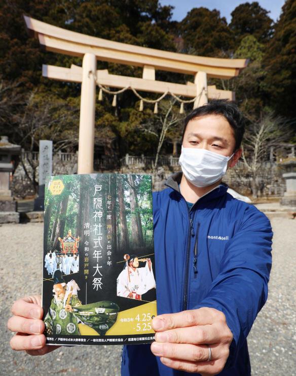 戸隠神社中社の大鳥居の前で公式ガイドブックを手にする観光協会職員