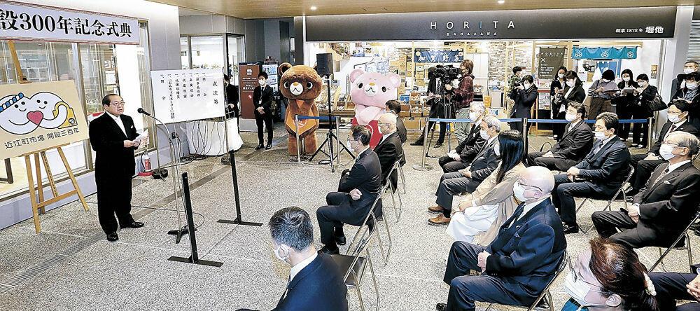 開設300年を祝い、あいさつする吉村理事長(左)=金沢市の近江町ふれあい館広場