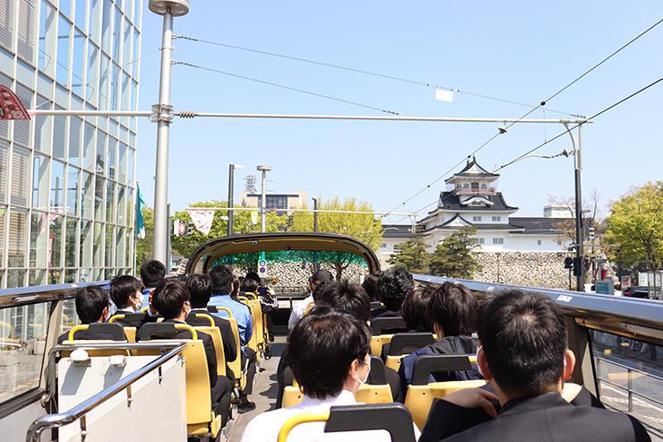 スカイバスから富山城を眺める乗客たち