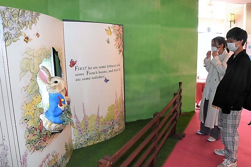ピーターラビットの展示を見る観光客