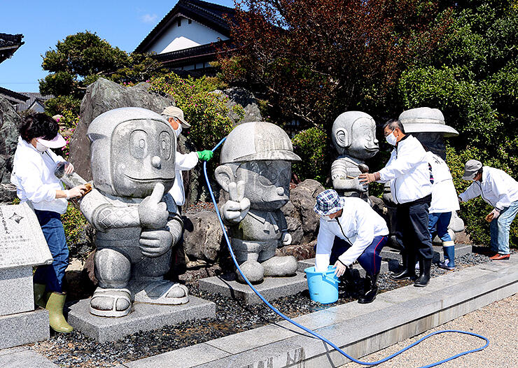 忍者ハットリくんらの石像4体を清掃する会員