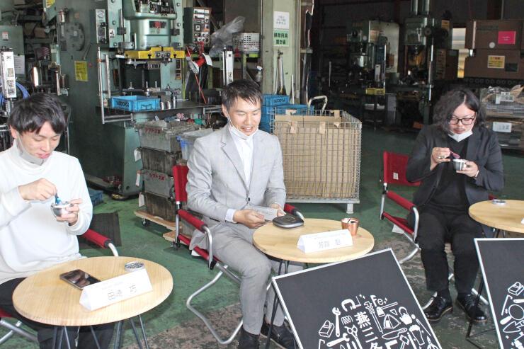 三条市内の工場で燕三条鉄アイスをPRする芳賀聡さん(中央)ら開発チームのスタッフ=同市北潟