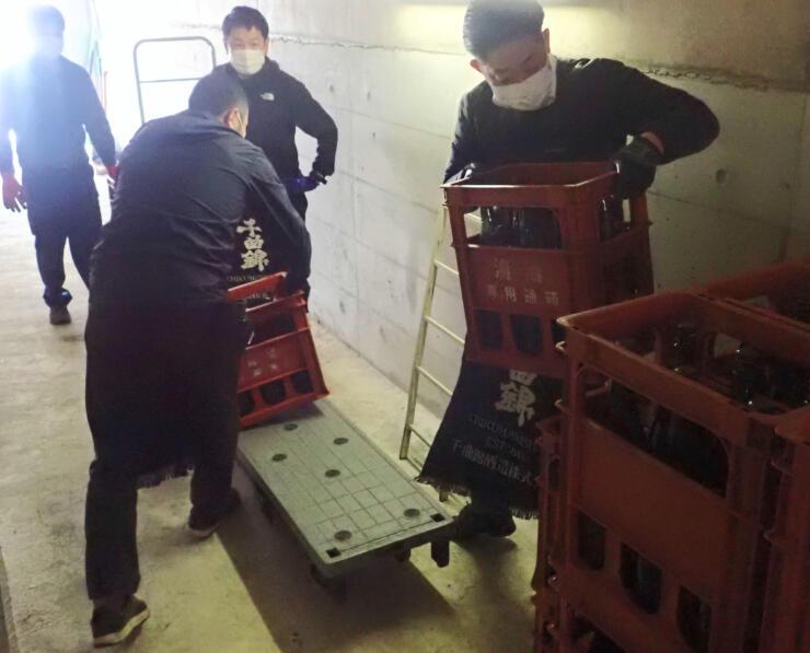 ダムの管理用通路に日本酒を運び込む社員ら