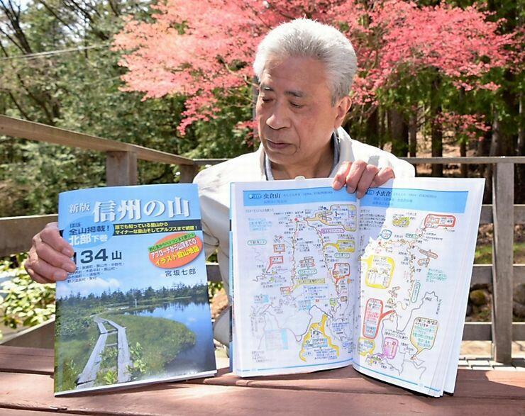 県北部の山を収録した「新版信州の山」を手にする宮坂さん。カラフルな手描きの地図で登山道などを紹介している