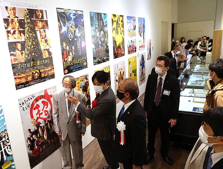 作品のポスターを見ながら映画について解説する本木さん(左から2人目)=高志の国文学館