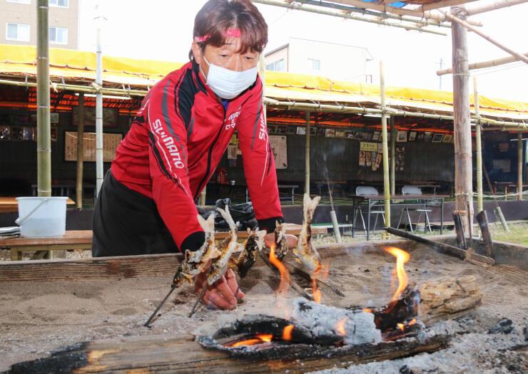 今季の営業を始めたつけ場小屋で、ウグイを焼く西沢さん