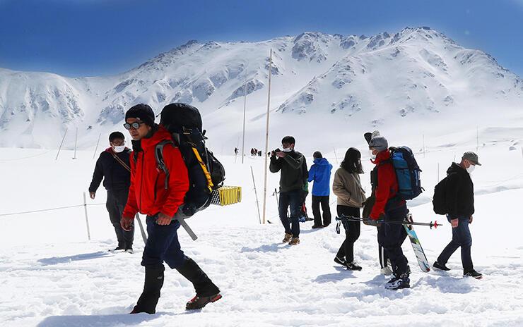 青空の下、雪原の散策を楽しむ観光客ら=立山・室堂