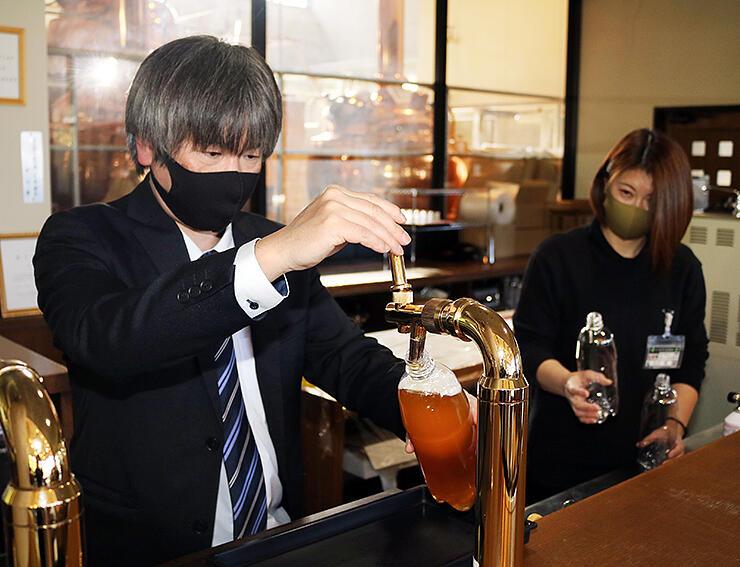 ペットボトルに宇奈月の地ビールを注ぐ清水支配人(左)