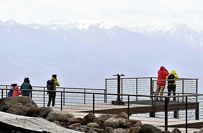 車山山頂のスカイテラスから八ケ岳連峰を眺める人たち=1日、茅野市