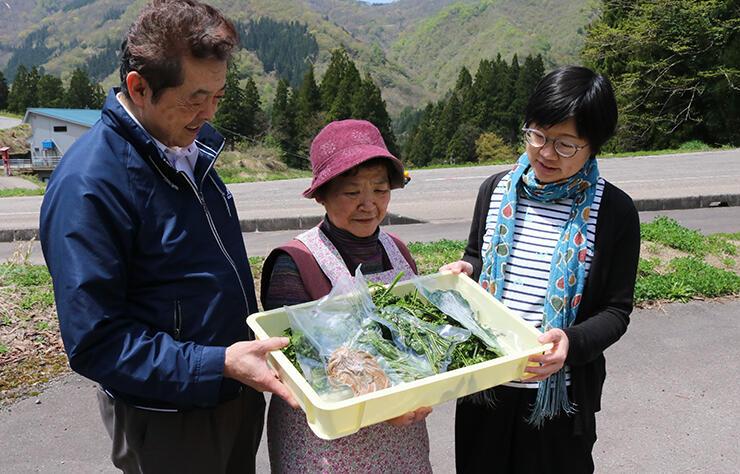 試作会で冷凍保存した山菜を手にする住民