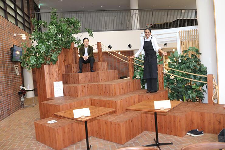 店内に登場した巨大ベンチ。左から前田社長、チャトウリカさん=立山町前沢のニルカレー