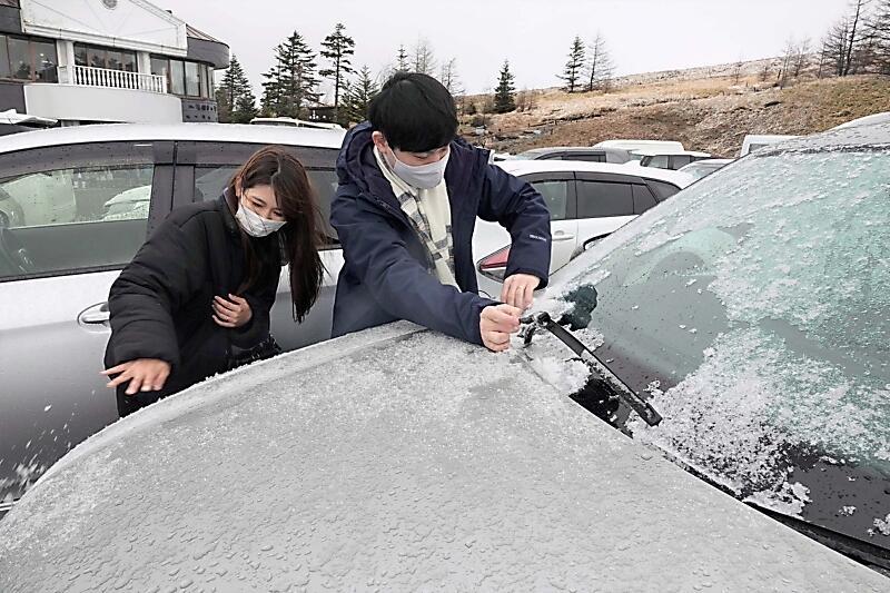車に積もった雪を払う石井さん夫婦=2日午前7時44分、長和町