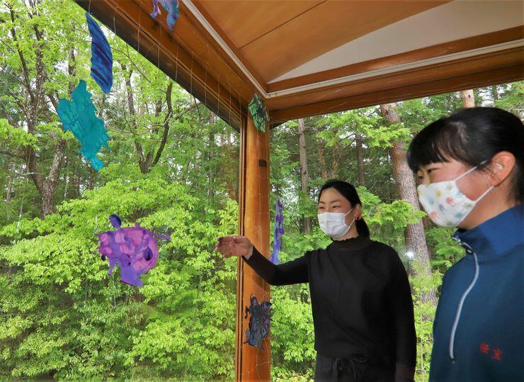 新緑を背景に参加者の作品を飾った小麻さん(左)