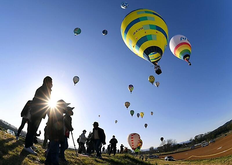 青空に浮上する熱気球。会場は無観客だったが、近くで見守る姿もあった=3日午前6時37分、佐久市鳴瀬(魚眼レンズ使用、秂弘樹撮影)