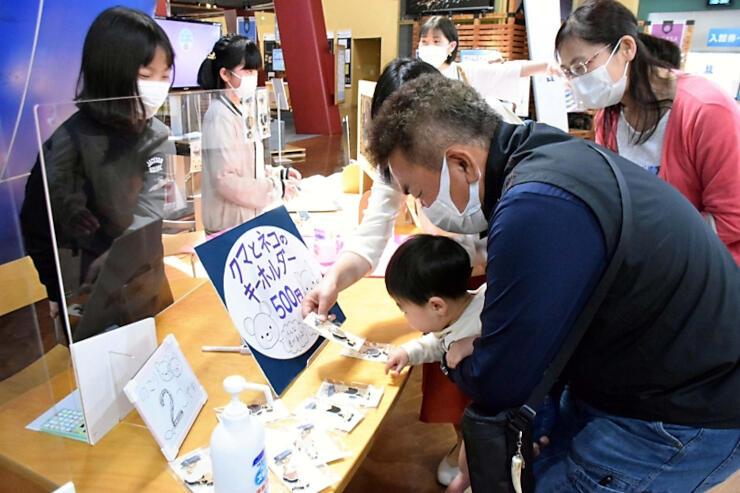地元の小学生(左側)が作った商品を手に取って眺める来場者たち