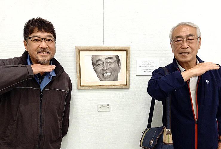 志村さんを描いた鉛筆画を挟んで写真に納まる知之さん(右)と古谷さん