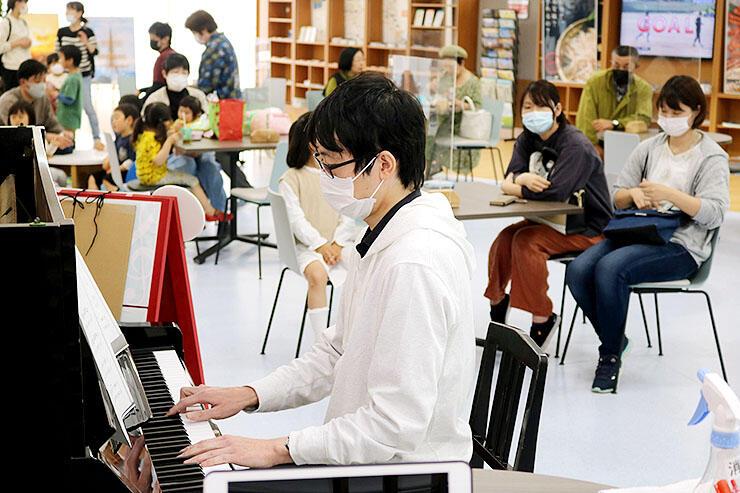 大勢が聴き入る中で、ピアノを弾く演奏者=クロスベイ新湊
