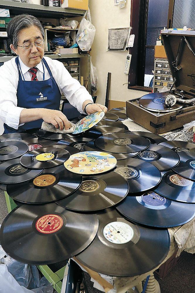 寄贈されたレコードを磨く八日市屋さん=金沢市尾張町2丁目の金沢蓄音器館
