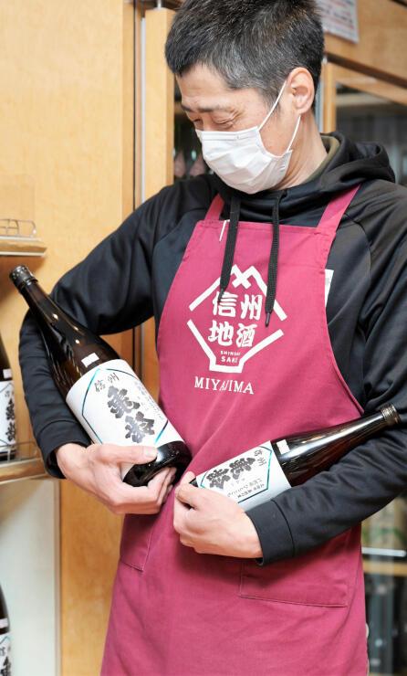 戸沢産米で醸造した純米吟醸酒を手にする宮島会長