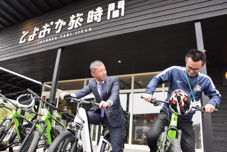 レンタルするeバイクに乗ってPRする福島さん(左)ら