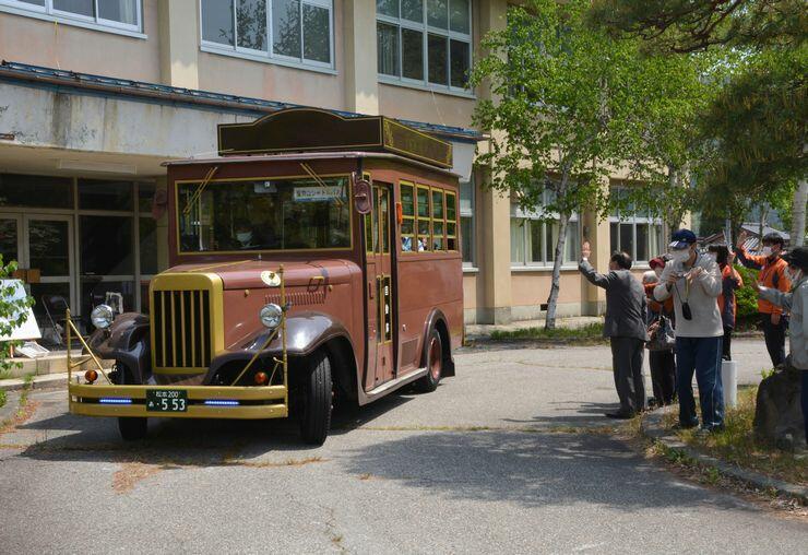 関係者に見送られて出発するボンネットバス=15日、大町市