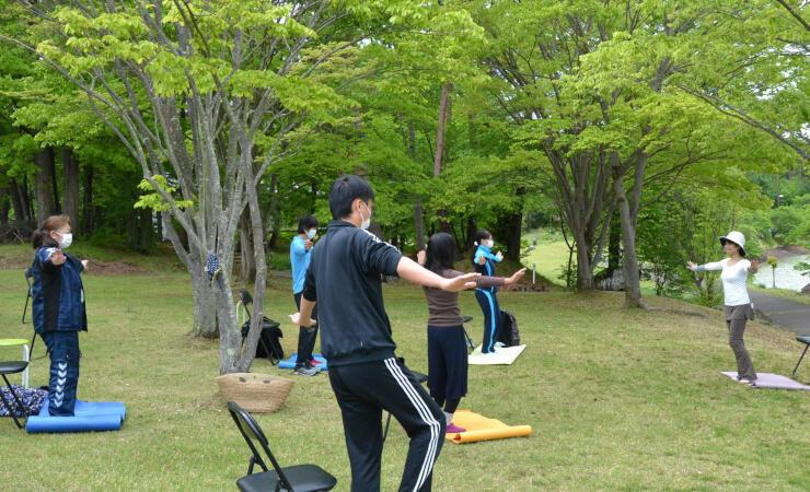 山中さん(右)の指導を受けながら運動をする参加者たち