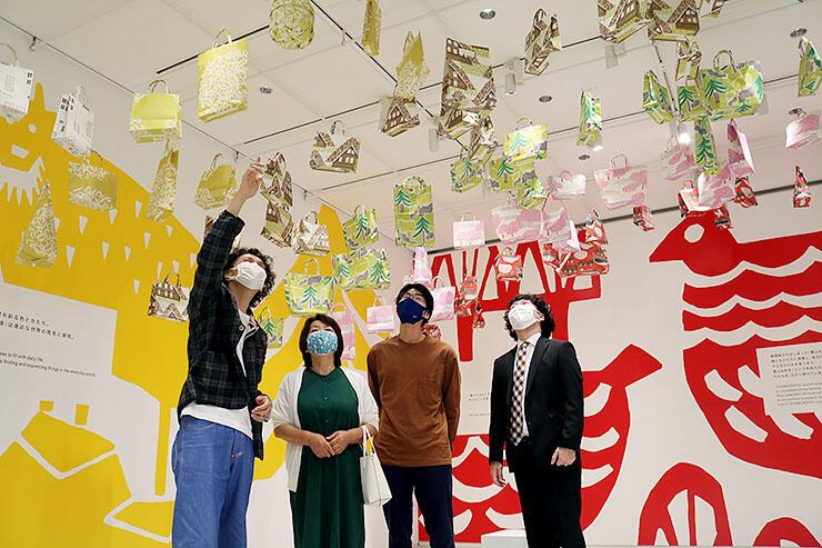天井にぶら下がるエコバッグを見上げる鈴木マサルさん(左)と来場者=県美術館1階TADギャラリー