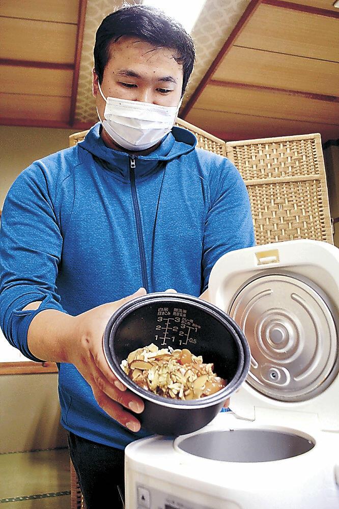 炊飯器の釜に具材を入れる高井さん=かほく市外日角の民宿
