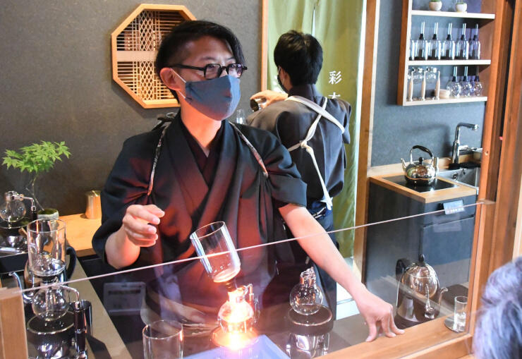 開店を前に公開した彩本堂で、サイホンでコーヒーを入れながらその魅力を語る中山さん=24日