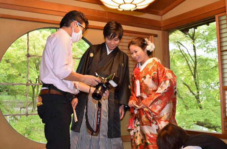 特徴的な円窓のある茶室で、撮影した写真を確認する新郎新婦