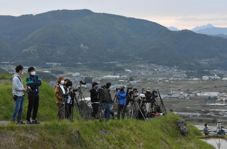姨捨の棚田で月食の撮影のタイミングを待つ参加者たち=26日午後6時51分