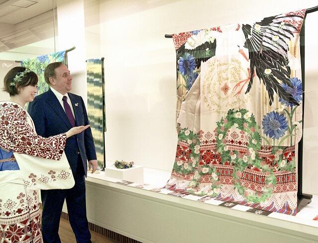 イエシン大使(右)にベラルーシを題材にした着物を紹介する奥野さん=5月25日、福井県越前市ふるさとギャラリー叔羅
