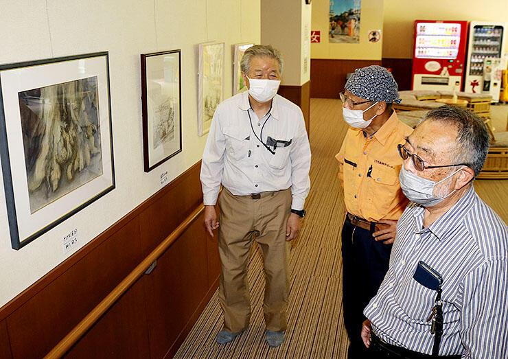 休憩ロビーで展覧会を開く遊彩会の(右から)米田さん、筧会長。左は白樺の湯の山森支配人