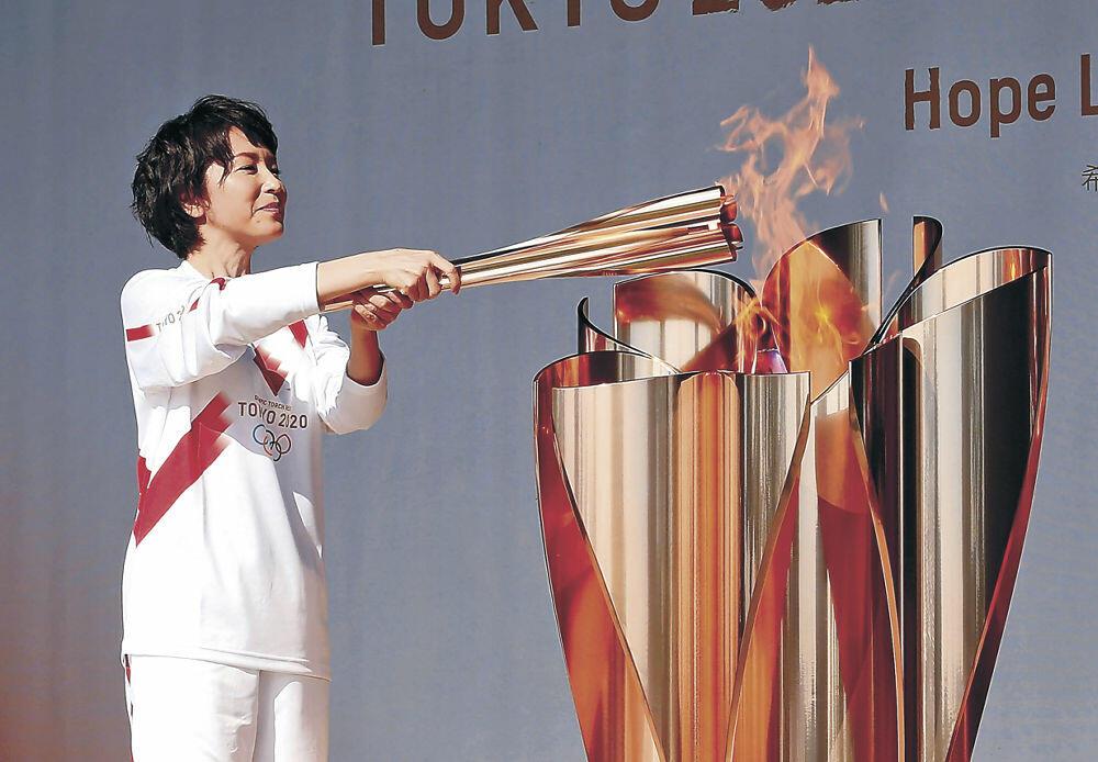 点火皿に聖火をともす若村麻由美さん=七尾市の和倉温泉湯っ足りパーク