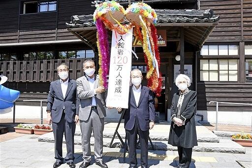 入館120万人の達成を祝ってくす玉を割り、記念撮影する関係者=6月1日、福井県勝山市のはたや記念館ゆめおーれ勝山前