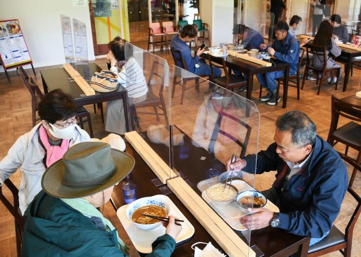 オープンした山ノ内大勝軒の夏季店でラーメンやつけ麺を食べる人たち