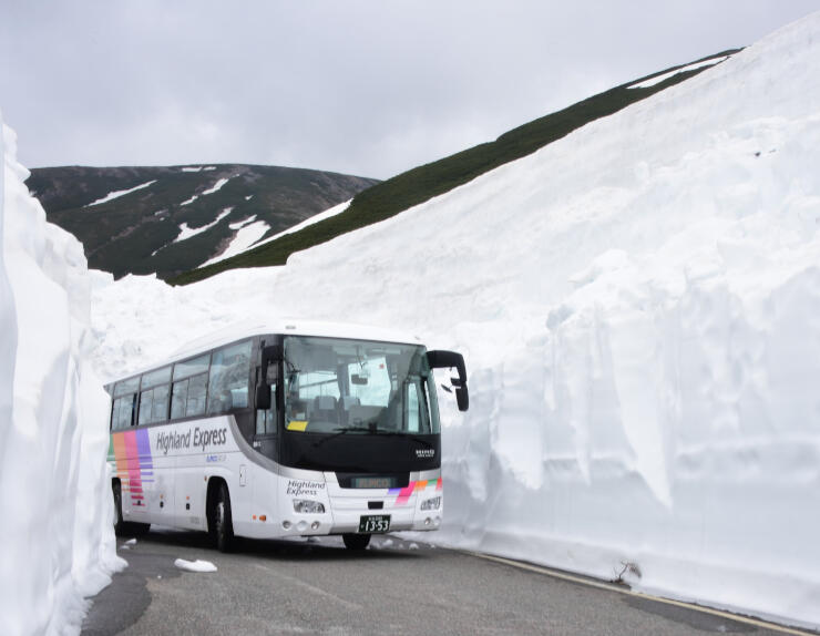 雪の壁の間を通る乗鞍岳春山バス