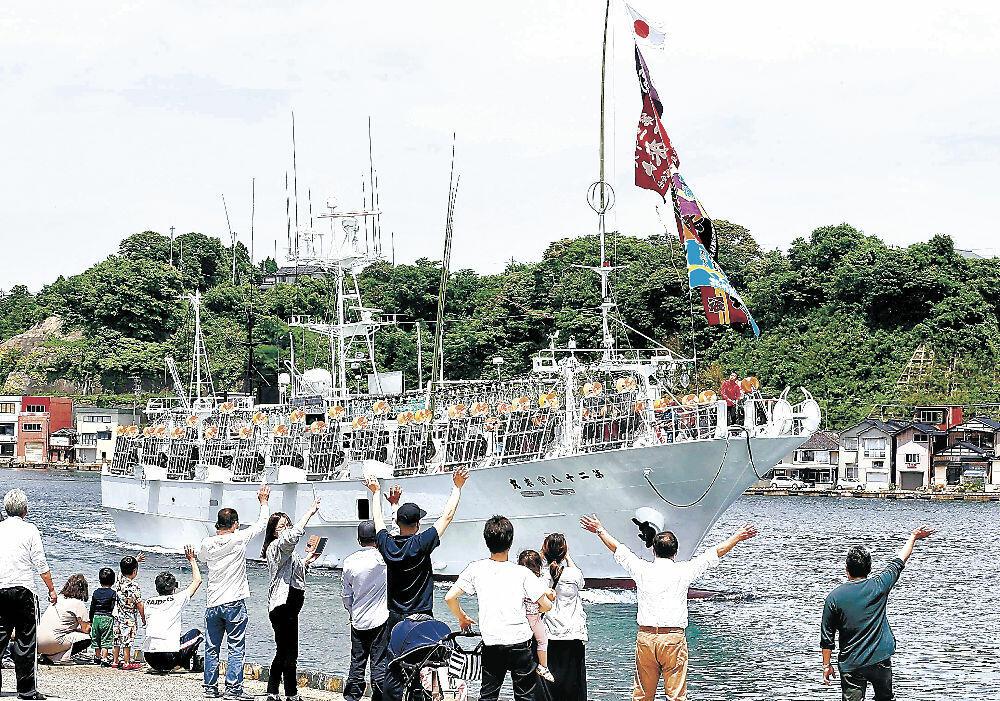 家族や住民の見送りを受けて出港する中型イカ釣り船=能登町小木港