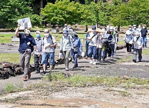 町屋などの跡が残る平面復原地区を歩く参加者=6月6日、福井県福井市の一乗谷朝倉氏遺跡