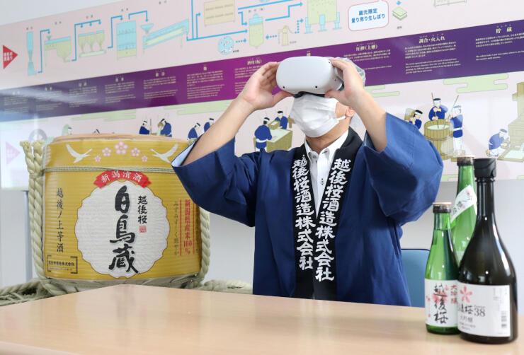 VRゴーグルを着けて見学方法を実演する越後桜酒造の羽澤清人社長=阿賀野市山口町1