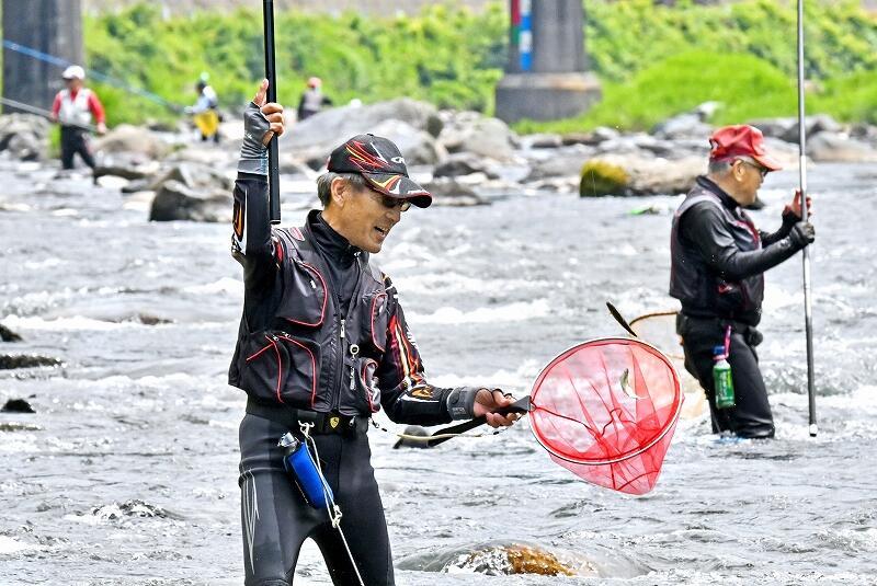 解禁初日、早速アユを釣り上げる釣り人=6月12日、福井県福井市大久保町の足羽川