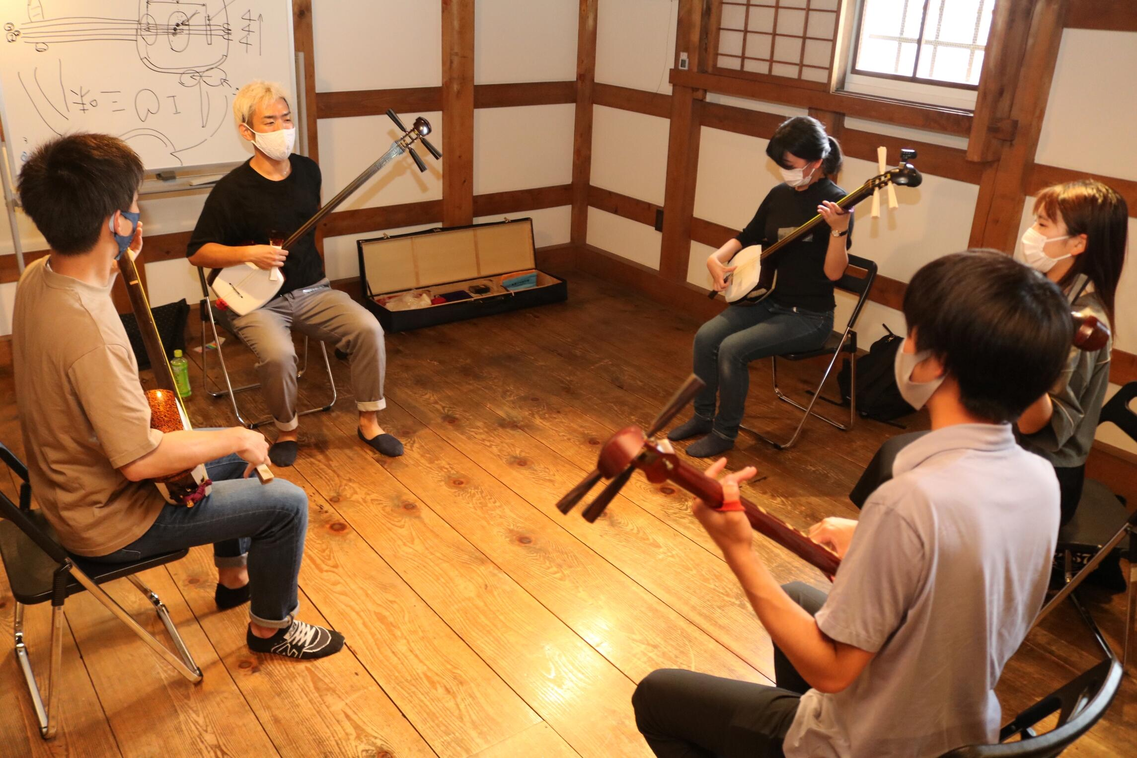 永村さん(左から2人目)に三味線の弾き方を教わる学生=金沢市片町2丁目