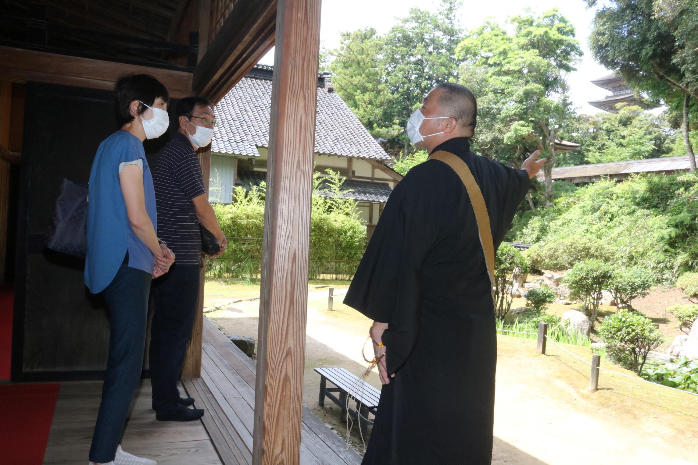 「御座之間」近くから五重塔や庭園を眺める拝観者=羽咋市の妙成寺