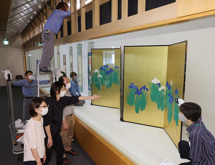 花を描いた屏風などが並ぶ会場で、照明の明るさを確認する学芸員ら=県水墨美術館