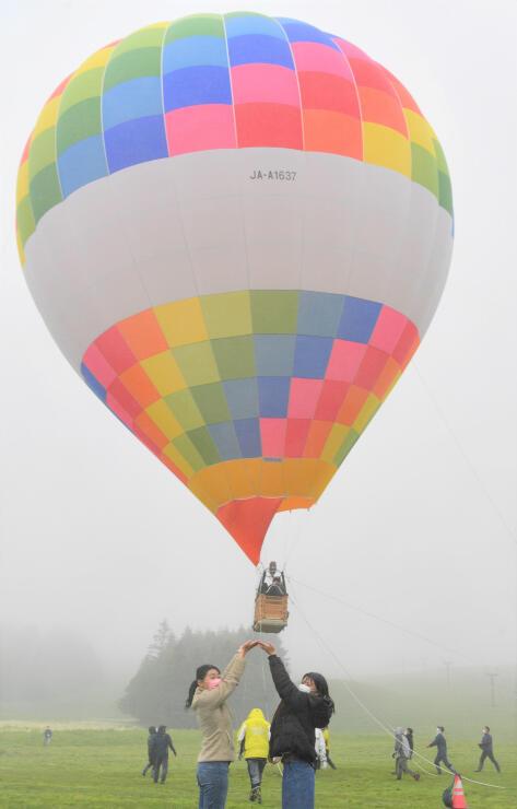浮かび上がる熱気球を背景に記念撮影する観光客