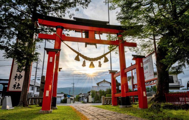 生島足島神社の東鳥居越しに昇る夏至の太陽。雲間から光が差し込んだ=21日午前5時36分、上田市下之郷