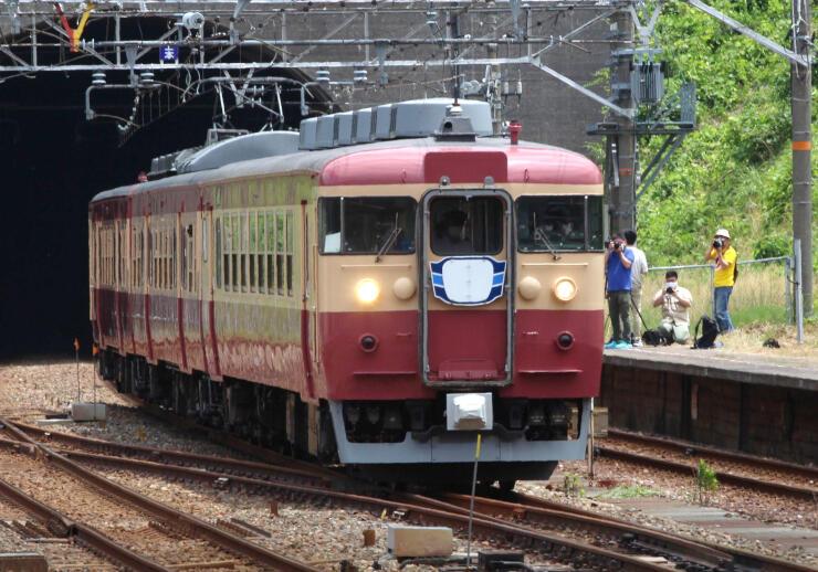 試運転で名立駅を通過する455系・413系電車。駅のホームには鉄道ファンらが駆け付けた=上越市名立区