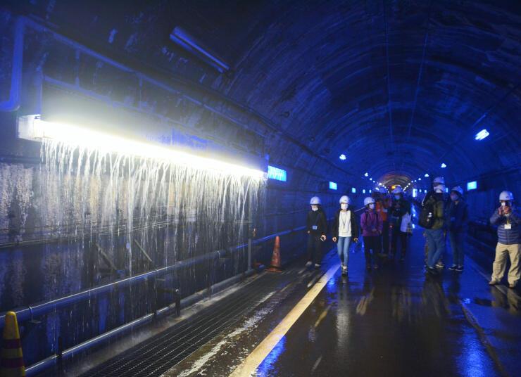 破砕帯の冷水を流している場所を見るツアー参加者ら