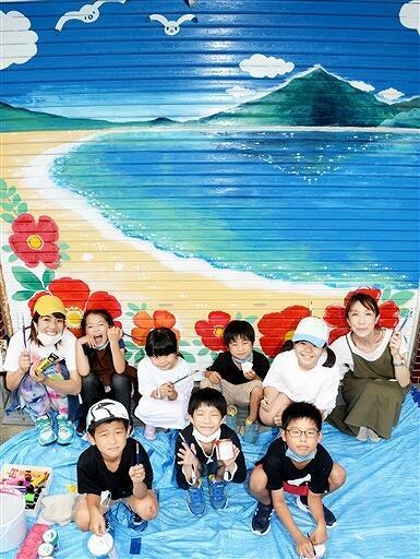 シャッターにハマナスを描いた子どもたちとchuncoさん(左)。右は浅野さん=6月28日、福井県高浜町三明