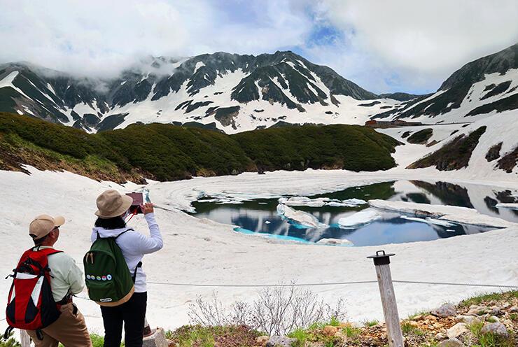 雲の切れ間から見える雄山(中央奥)と雪解けが進むみくりが池=立山・室堂平